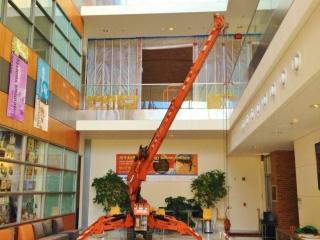 Jekko mini crane lifting beams inside an academic building.