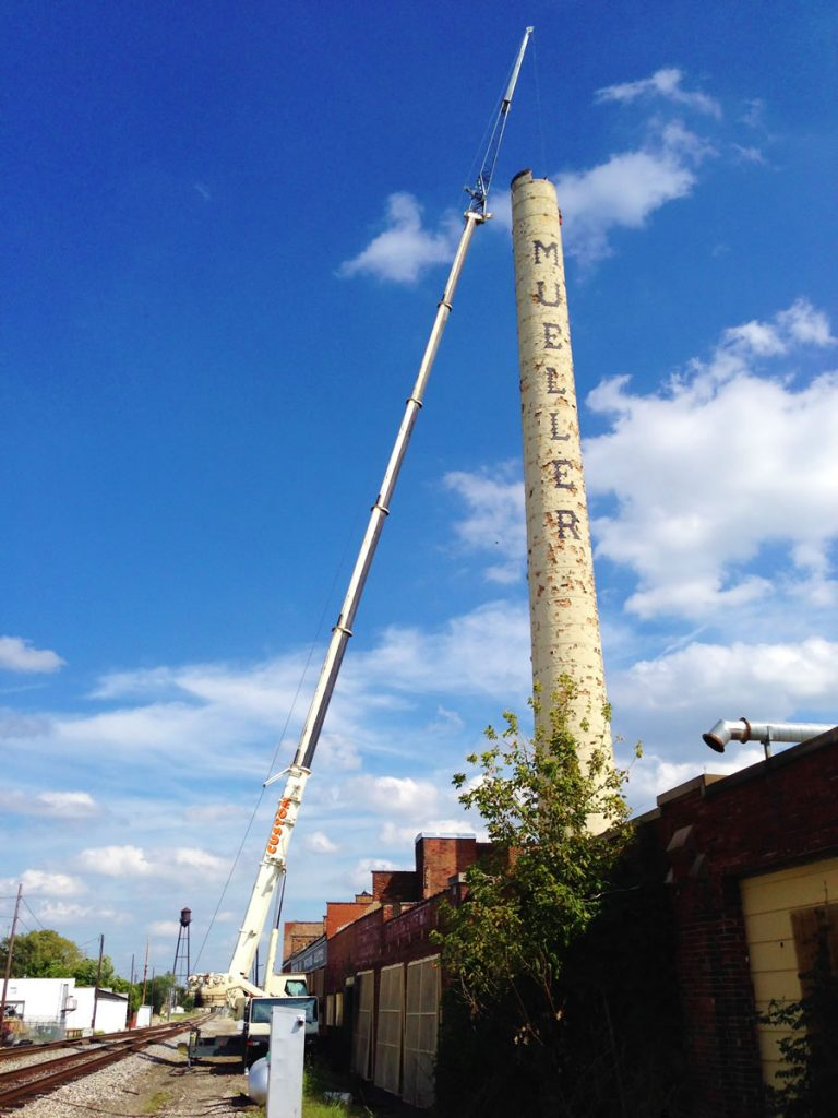 Smoke stack is being deconstructed by a 90 ton hydraulic crane.