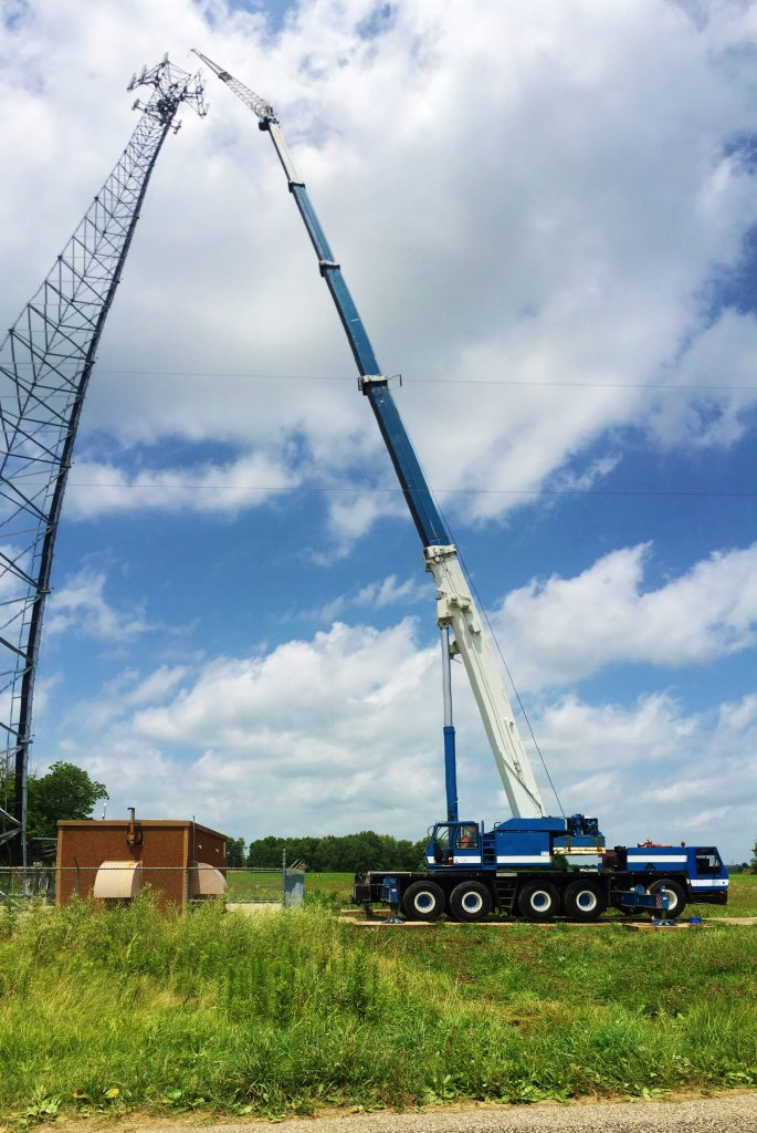175 ton crane reaches high to hoist new antennas for a cell tower.