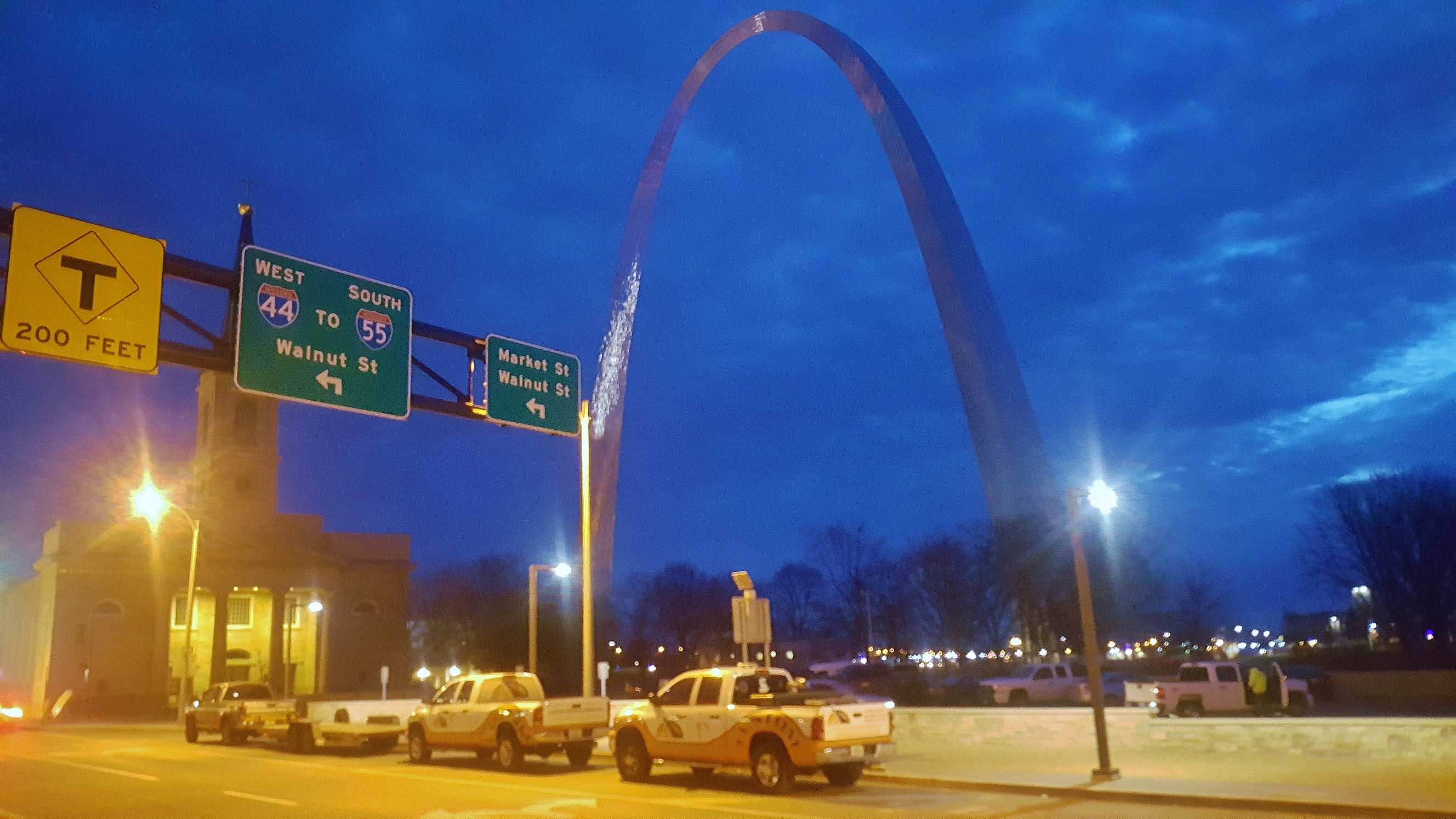 Three Custom Service Crane trucks and a trailer are parked in front of the St. Louis Arch.