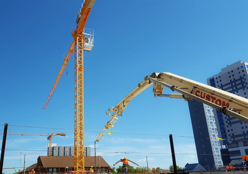 CSCs 39 meter pump truck, tower cranes, and employees work hard at apartment complex in Champaign, IL.