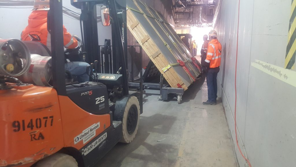 Two forklifts are rigged on both sides of the heavy cart to transport it down the narrow hallway.